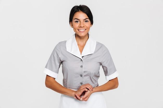Retrato de empregada muito sorridente em uniforme, mantendo as mãos juntas
