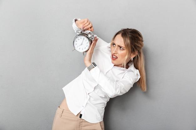 Retrato de empresária chateada, gritando e segurando o despertador no escritório, isolado