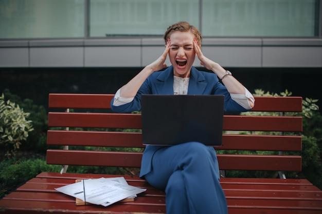 Retrato de empresária estressante gritando. ela segura a cabeça dele com as mãos