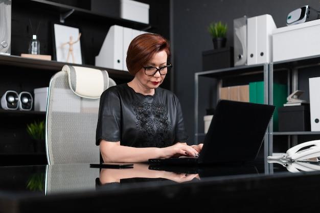 Retrato de empresária estrita com laptop no escritório elegante