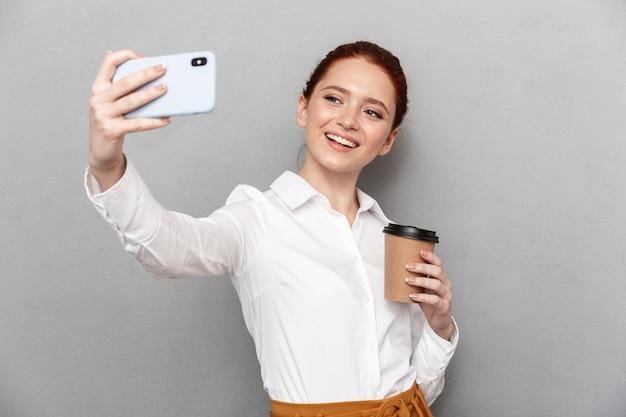 Retrato de empresária ruiva feliz tirando foto de selfie no smartphone no escritório e bebendo café para viagem em um copo plástico isolado sobre cinza