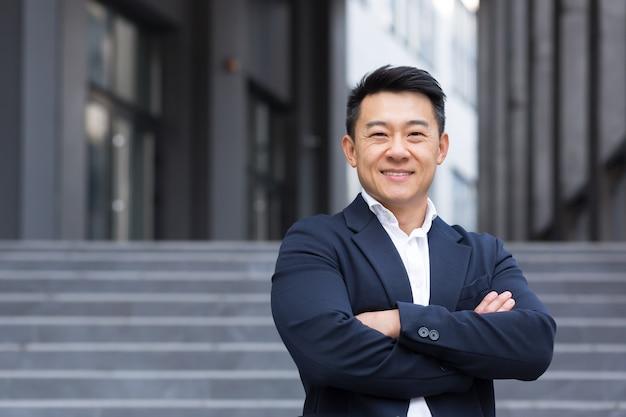 Retrato de empresário asiático alegre e bem-sucedido perto do escritório em terno de negócio confiante gerente vendedor corretor sorrindo