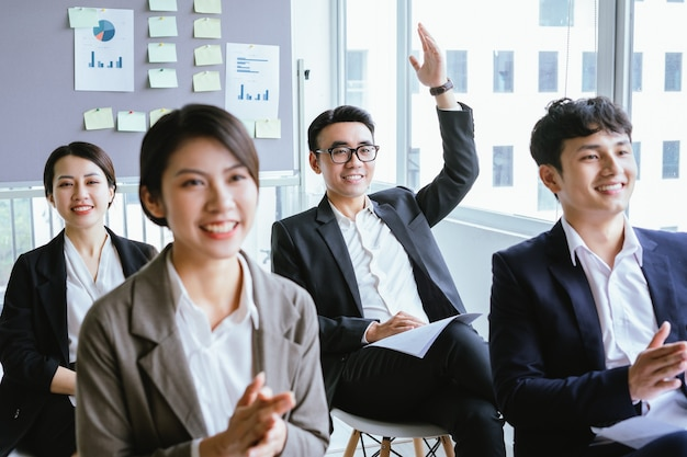 Retrato de empresário asiático levantando a mão para dar sua opinião na reunião