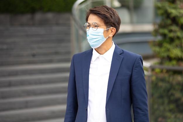 Retrato de empresário asiático usando máscara protetora para prevenir o vírus covid-19 ao ar livre na cidade.