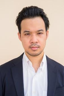 Retrato de empresário asiático vestindo terno ao ar livre contra um fundo liso