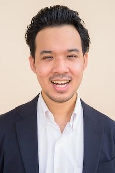 Retrato de empresário asiático vestindo terno contra um fundo liso enquanto sorri