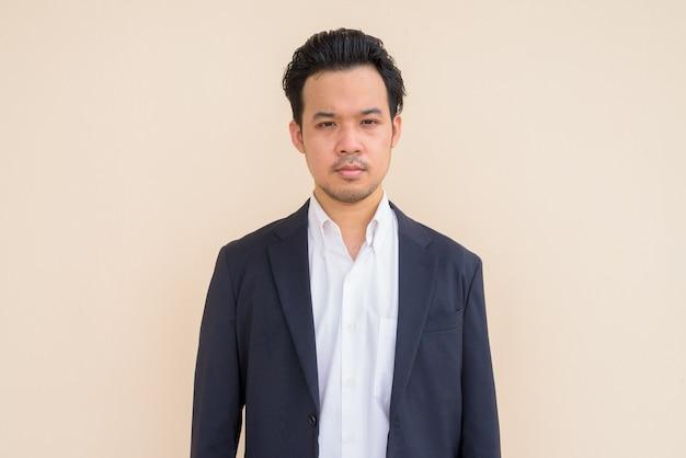 Retrato de empresário asiático vestindo terno contra um fundo simples