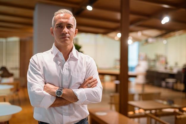 Retrato de empresário bonito com os braços cruzados em foto horizontal de cafeteria com espaço de cópia