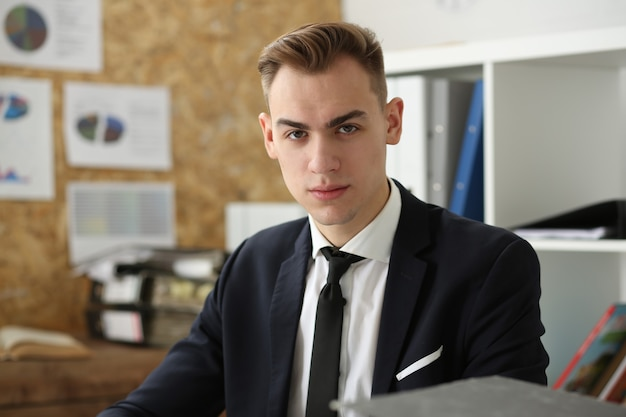 Retrato de empresário bonito no local de trabalho, olhando diretamente de mãos cruzadas.