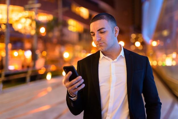 Retrato de empresário bonito vestindo terno ao ar livre à noite na cidade