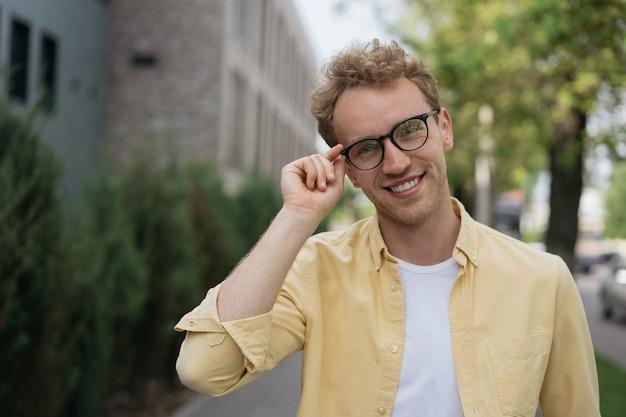 Retrato de empresário confiante usando óculos elegantes de camisa amarela em pé na rua