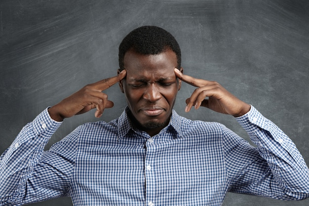 Retrato de empresário de pele escura com forte dor de cabeça, pressionando os dedos nas têmporas, fechando os olhos e fazendo caretas com expressão dolorida.
