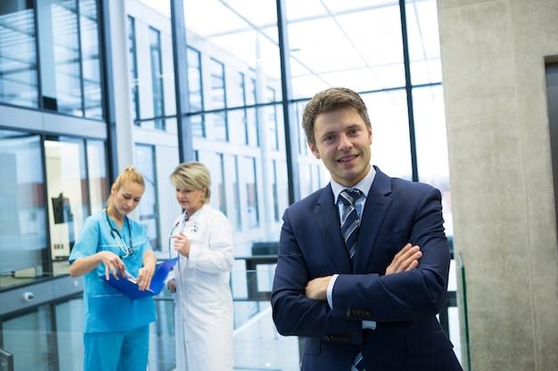 Retrato de empresário em pé com os braços cruzados no corredor