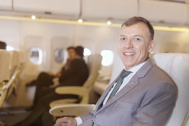 Retrato de empresário em um avião, passageiro relaxante Foto Premium