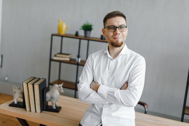 Retrato de empresário feliz sorridente de óculos e camisa branca no escritório após um árduo dia de trabalho