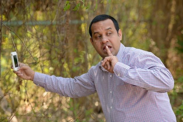 Retrato de empresário indiano com cabelo curto relaxando no parque ao ar livre