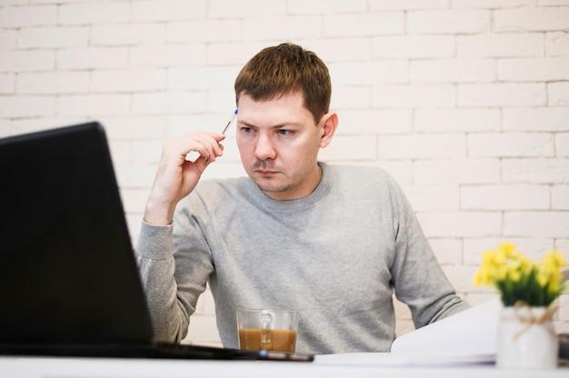 Retrato de empresário inteligente, trabalhando em casa