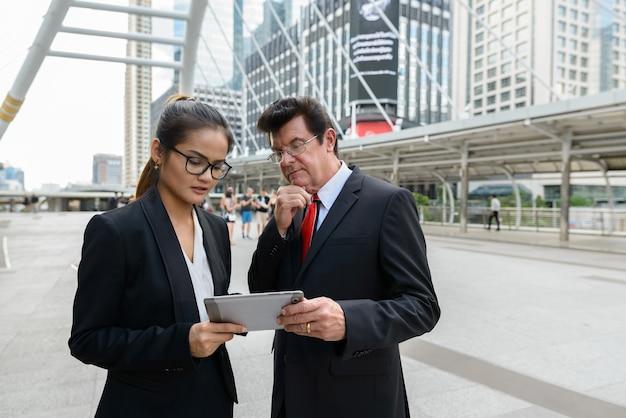 Retrato de empresário maduro e jovem empresária asiática juntos como conceito de diversidade de equipe ao ar livre da cidade