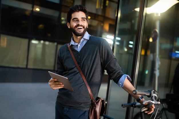 Retrato de empresário segurando tablet e bicicleta ao ar livre