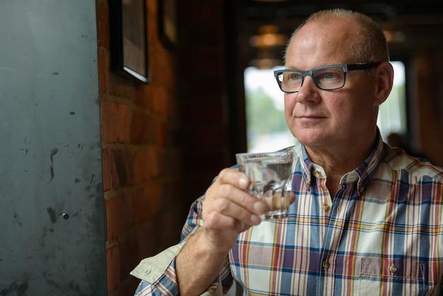 Retrato de empresário sênior bebendo água no café
