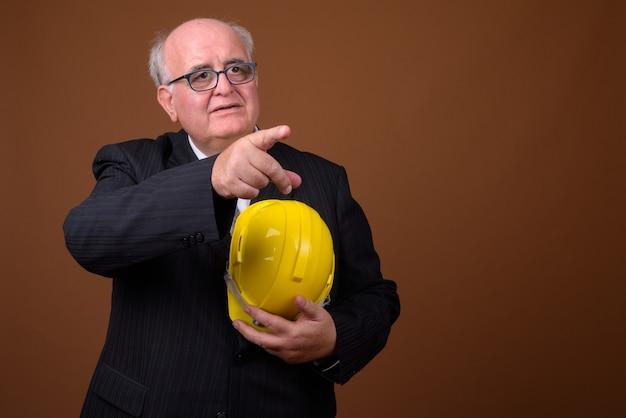 Retrato de empresário sênior com excesso de peso e capacete de segurança