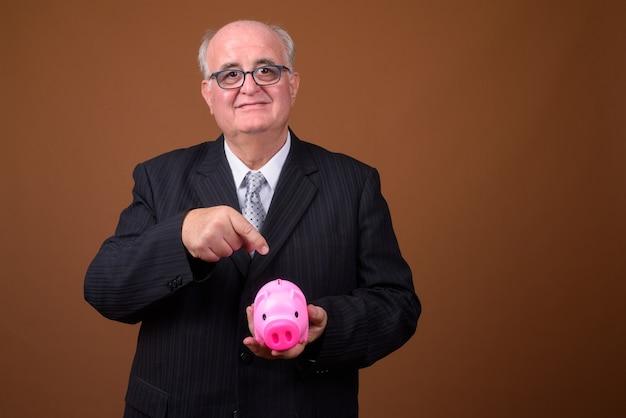 Retrato de empresário sênior com excesso de peso segurando o cofrinho