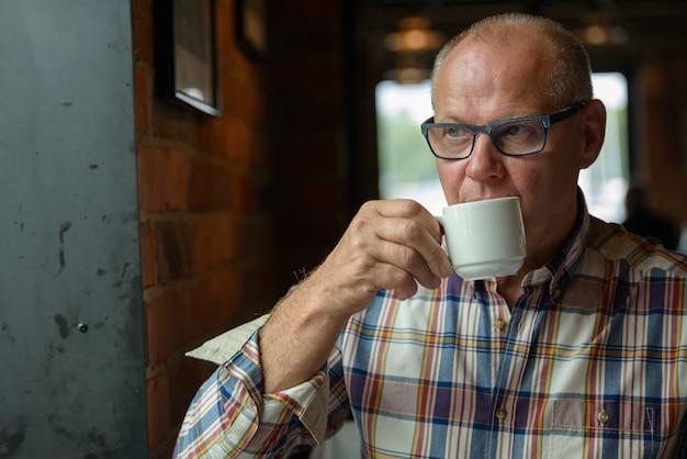 Retrato de empresário sênior pensando enquanto bebe café