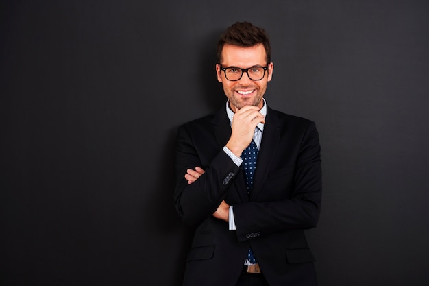 Retrato de empresário sorridente usando óculos