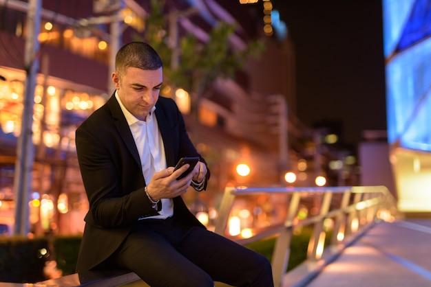 Retrato de empresário usando telefone celular à noite na cidade enquanto está sentado