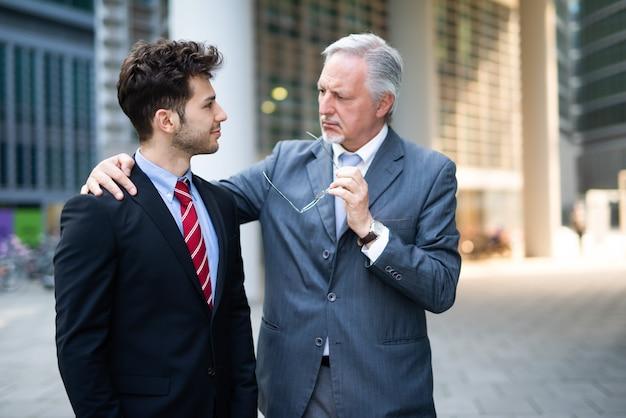 Retrato de empresários discutindo ao ar livre