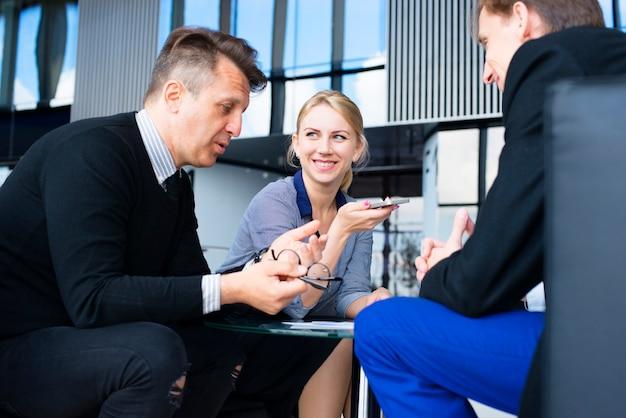 Retrato de empresários felizes conversando no intervalo em um café sentados juntos à mesa