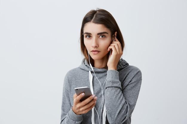Retrato de encantadora garota caucasiana, com cabelos longos escuros no elegante capuz cinza usando fones de ouvido, procurando música para ouvir no smartphone, com expressão calma do rosto.