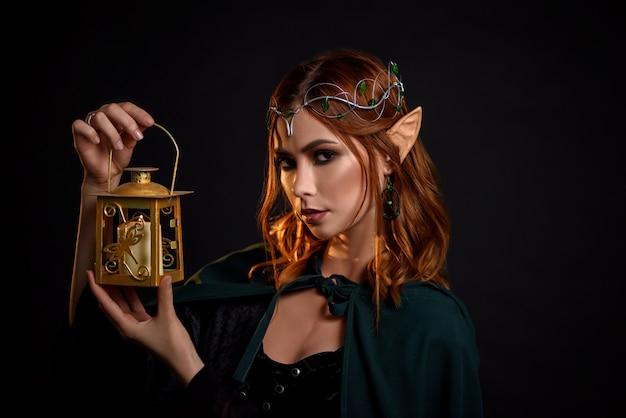 Retrato de encantadora garota mística com cabelo vermelho na capa.