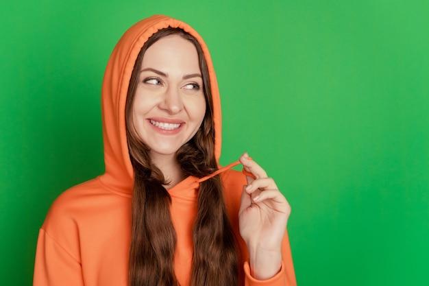Retrato de encantadora senhora curiosa olhando para o lado, espaço em branco, usar capuz sobre fundo verde