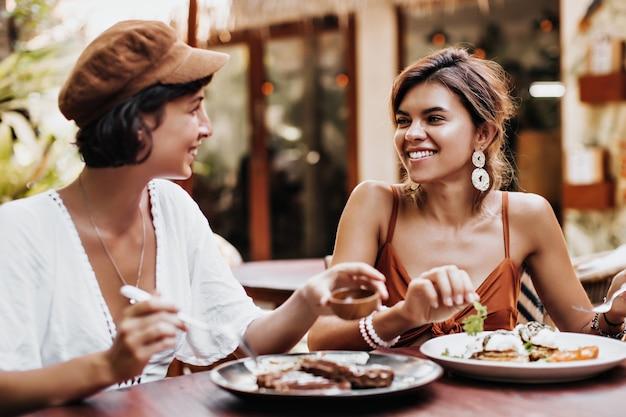 Retrato de encantadoras mulheres bronzeadas de bom humor comendo comida saborosa em um café de rua