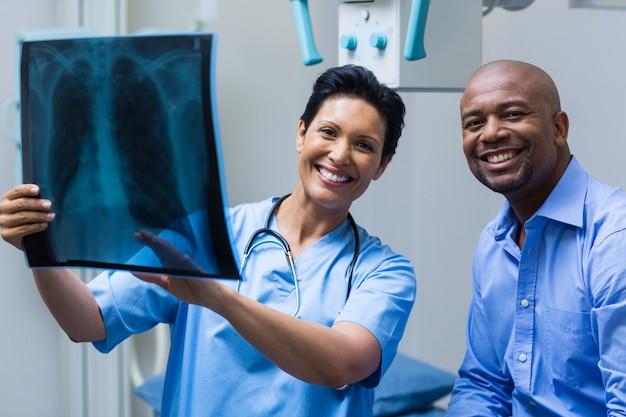 Retrato de enfermeira e paciente discutindo raio-x