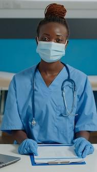 Retrato de enfermeira médica olhando para a câmera com máscara facial