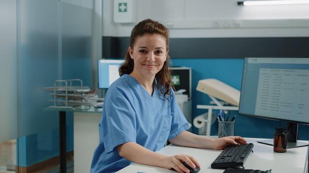 Retrato de enfermeira usando o computador para consultas com o paciente