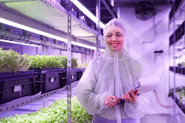 Retrato de engenheira agrícola sorrindo alegremente enquanto posava na estufa do viveiro de plantas iluminada por luz azul, copie o espaço