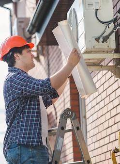 Retrato de engenheiro com capacete de segurança olhando no plano do sistema de ar condicionado