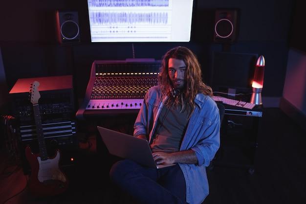 Retrato de engenheiros de áudio usando laptop