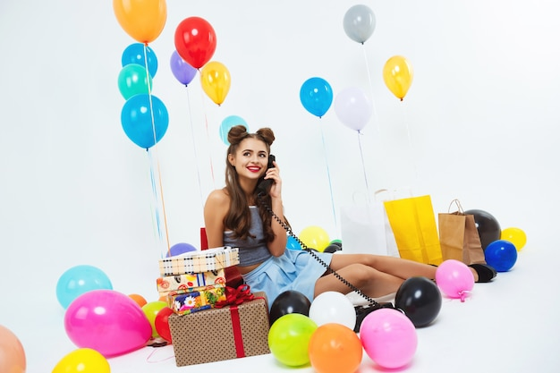 Retrato de engraçadinha, tendo a conversa por telefone, sentada no chão