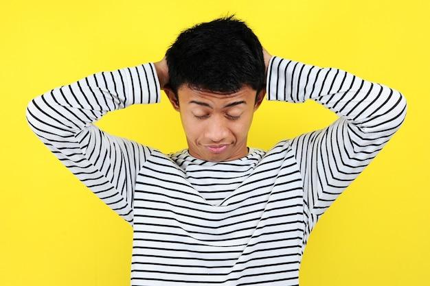 Retrato de engraçado homem asiático, mostrando um gesto com sono. sensação de cansaço do trabalho duro, isolado no fundo amarelo