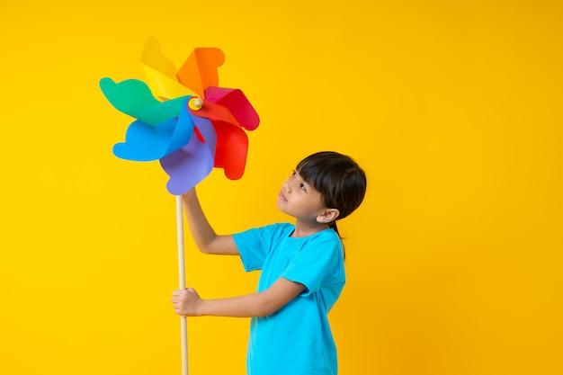 Retrato de engraçado jovem asiática tailandesa menina bonita segurando e jogando turbina colorida