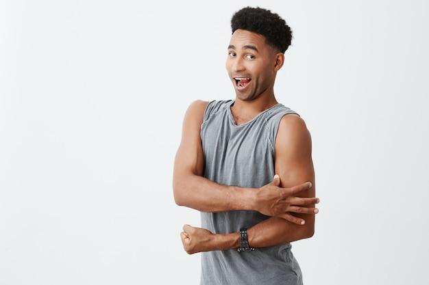 Retrato de engraçado jovem homem africano de pele escura com cabelos cacheados em desgaste desportivo cinza tocando seus músculos com a mão, olhando na câmera com expressão boba. conceito de esporte