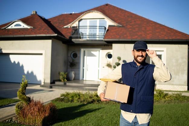 Retrato de entregador profissional em frente a casa entregando pacotes