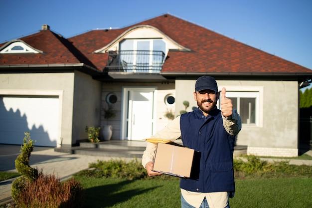 Retrato de entregador profissional segurando o polegar para cima e entregando pacotes no endereço