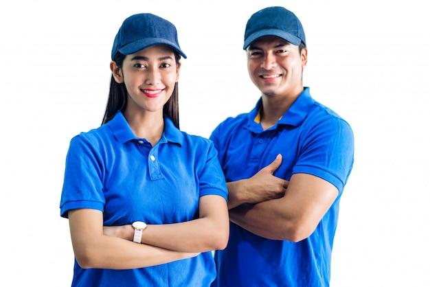 Retrato de entregador sorridente e mulher com os braços cruzados em uniforme azul isolado