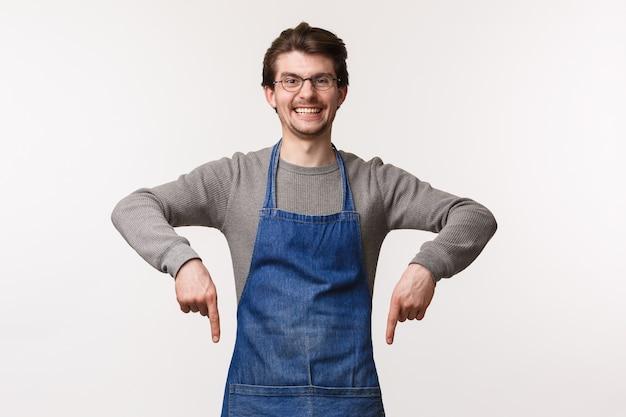 Retrato de entusiasmado e sorridente empregado masculino convidar os clientes a visitar sua loja, desfrutar de deliciosos cafés e sobremesas, apontando os dedos para baixo, sorrindo para a câmera, usar avental por cima da camisa