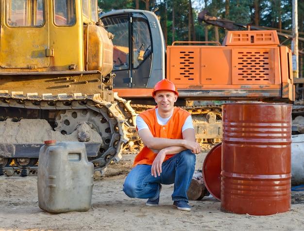 Retrato de equipamento de construção de motorista sentado perto de tambores de combustível